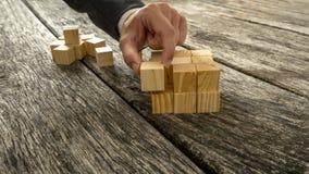 Primo piano dell'uomo d'affari che monta i cubi di legno in bianco in uno stru Fotografia Stock