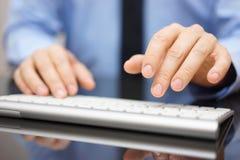 Primo piano dell'uomo d'affari che scrive sulla tastiera di computer moderna Fotografia Stock