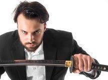 Primo piano dell'uomo d'affari con la spada sopra fondo bianco Fotografie Stock Libere da Diritti