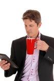Primo piano dell'uomo d'affari con la tazza rossa fotografie stock