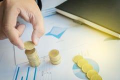 Primo piano dell'uomo d'affari Hand Put Coins alla pila di monete sul fina Immagine Stock Libera da Diritti