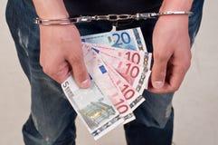 Primo piano dell'uomo delle mani in manette che tengono soldi Immagini Stock Libere da Diritti