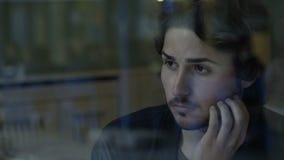 Primo piano dell'uomo sollecitato di affari che pensa e che si siede vicino alla finestra di vetro in una gente del pub che passa archivi video