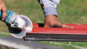 Primo piano dell'uomo in vestiti da lavoro che tagliano una lista di tetto d'acciaio rosso dalla sega per il taglio di metalli cl stock footage