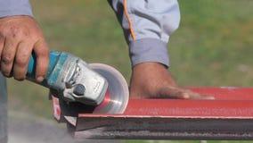 Primo piano dell'uomo in vestiti da lavoro che tagliano una lista di tetto d'acciaio rosso dalla sega per il taglio di metalli cl archivi video