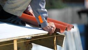 Primo piano dell'uomo in vestiti da lavoro con il trapano elettrico che installa le mattonelle rosse del metallo sulla casa di le immagini stock libere da diritti