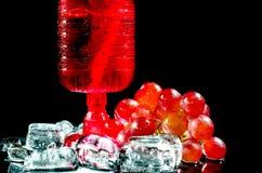 Primo piano dell'uva del vino rosso di vetro un fondo nero Fotografia Stock