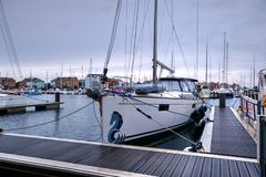 Primo piano dell'yacht attraccato in porto sovrano con gli yacht, le barche e gli appartamenti di Nuovo-configurazione nel fondo fotografia stock libera da diritti