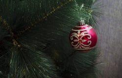 Primo piano della bagattella rossa che pende da un albero di Natale decorato o da una palla astratta del nuovo anno con superfici Immagini Stock Libere da Diritti