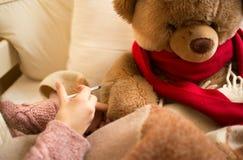 Primo piano della bambina che fa iniezione all'orsacchiotto malato Fotografia Stock