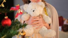 Primo piano della bambina che sta vicino all'albero di abete decorato e che tiene orsacchiotto video d archivio