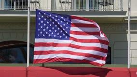 Primo piano della bandiera americana che fluttua sul palo in forte vento davanti a costruzione archivi video