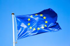 Primo piano della bandiera di UE sul cielo blu del fondo fotografia stock