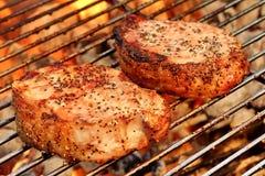 Primo piano della bistecca della carne di maiale due sulla griglia ardente del BBQ Fotografia Stock