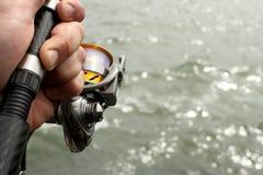 Primo piano della bobina di pesca a disposizione Fotografia Stock