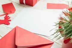 Primo piano della carta di carta in bianco bianca con la busta rossa su fondo bianco Immagine Stock
