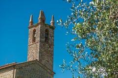 Primo piano della chiesa e del campanile con gli alberi intorno nel villaggio di Monteriggioni Fotografia Stock