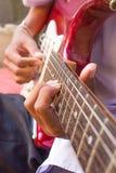 Primo piano della chitarra elettrica con le dita che lo giocano Fotografia Stock