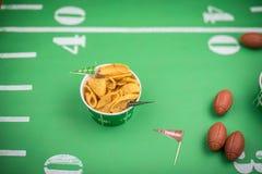 primo piano della ciotola di carta di chip di cereale sul campo verde con l'iarda Lin Fotografie Stock