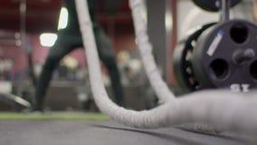 Primo piano della corda per un crossfit, con cui un uomo si esercita nella palestra stock footage