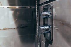 Primo piano della doccia e rubinetto nel bagno fotografie stock libere da diritti