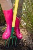Primo piano della donna che allenta suolo con la forcella del giardino Fotografia Stock