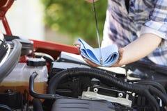 Primo piano della donna che controlla il livello di olio per motori dell'automobile sull'asta misura-livello Immagine Stock