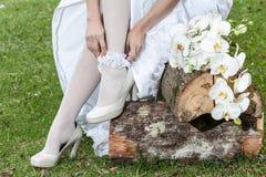 Primo piano della donna che dispone lega con le scarpe e mazzo dei fiori fotografie stock