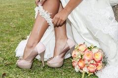 Primo piano della donna che dispone lega con le scarpe e mazzo dei fiori fotografia stock