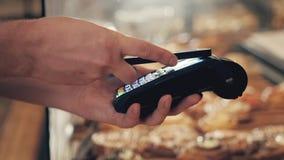 Primo piano della donna che effettua pagamento con NFC in forno, ristorante del caffè, paga senza contatto del telefono cellulare Fotografie Stock