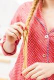 Primo piano della donna che fa treccia su capelli biondi fotografie stock libere da diritti