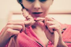 Primo piano della donna che fa treccia su capelli biondi fotografia stock