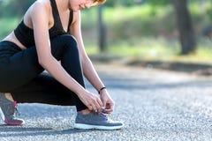 Primo piano della donna che lega i laccetti Corridore femminile g di forma fisica di sport Fotografie Stock