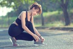 Primo piano della donna che lega i laccetti Corridore femminile g di forma fisica di sport Fotografie Stock Libere da Diritti