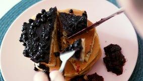Primo piano della donna che mangia i pancake delle bacche con il coltello e la forcella, prima colazione di mattina archivi video