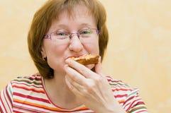 Primo piano della donna che mangia la fetta della pizza Fotografie Stock Libere da Diritti