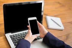 Primo piano della donna che per mezzo del computer portatile e dello smartphone Immagini Stock Libere da Diritti