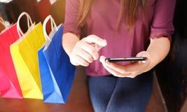 Primo piano della donna che per mezzo del suo smartphone durante l'acquisto fotografia stock