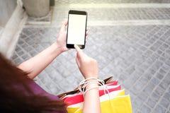 Primo piano della donna che per mezzo del suo smartphone durante l'acquisto fotografia stock libera da diritti