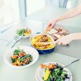 Primo piano della donna che prepara cena con il pollo arrostito con il servizio della patata con le insalate verdi Fotografia Stock Libera da Diritti