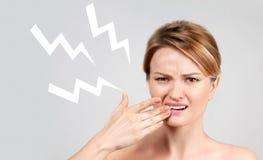 Primo piano della donna che soffre dal mal di denti immagini stock libere da diritti