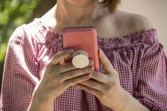 Primo piano della donna che tiene e che legge da un telefono cellulare in caso rosa con la maniglia della presa su per recedere l immagine stock libera da diritti