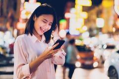 Primo piano della donna che tiene uno smartphone alla notte sulla strada dei negozi della citt? e sulla passeggiata della gente fotografia stock