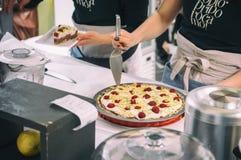 Primo piano della donna che tratta torta di formaggio con il server della torta al mercato aperto dell'alimento a Transferrina, S fotografia stock