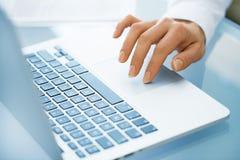Primo piano della donna della mano che per mezzo di un computer portatile Immagine Stock