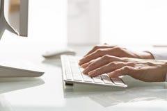Primo piano della donna delle mani che per mezzo di un computer della tastiera Immagini Stock