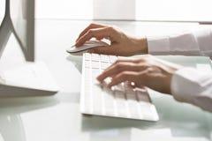 Primo piano della donna delle mani che per mezzo di un topo e di una tastiera Fotografie Stock