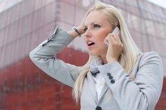 Primo piano della donna di affari colpita che comunica sul telefono cellulare contro l'edificio per uffici Fotografie Stock Libere da Diritti
