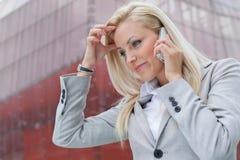 Primo piano della donna di affari confusa che comunica sul telefono cellulare contro l'edificio per uffici Fotografie Stock