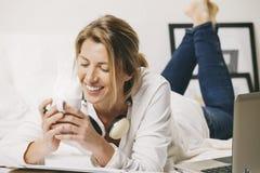 Primo piano della donna di affari maturi con la tazza di caffè nel letto. Fotografia Stock